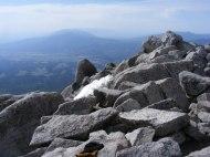 From Mount Shavano are seen the distant Sangre de Cristo Mountains under a shroud of haze