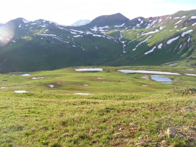 """From the """"small"""" knoll, my tent can barely be seen just above the snow patch to the left of the snow patch above the small pond to the right"""