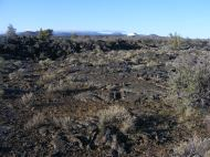 Lava flow near Black Crater, Lava Beds National Monument. Some clouds linger over the higher peaks
