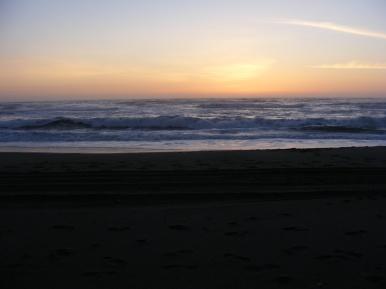 Waves crashing ashore as the sun sets, Gold Bluff Beach