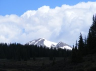 Blue sky, puffy clouds, snow-clad peaks and dark conifer forests... a ubiquitous Rocky Mountain vista in mid-June