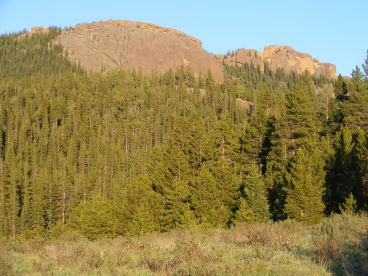 Golden hued sunlight strikes the red granite outcroppings above East Lost Park