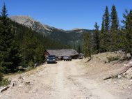 Vehicles near the old boarding house-type structure in Pomeroy Gulch