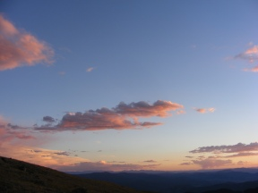Clouds lit up over the Great Divide at sunset, as seen from Mount Peck