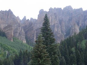 Cliffs of breccia, rising above the forest of aspen and conifer, East Fork Cimarron River in the Uncompahgre Wilderness