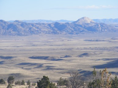 The weathered granitic rock of the Granite Mountains in the valley of Sweetwater River, Rattlesnake Hills beyond