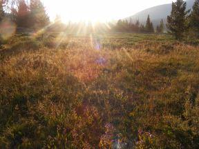 Golden shafts of light streaking across the Roaring Fork Basin at sunset