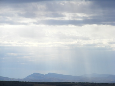 Looking east from a pullout on U.S. 191, distant mountains with sunlight streaking down